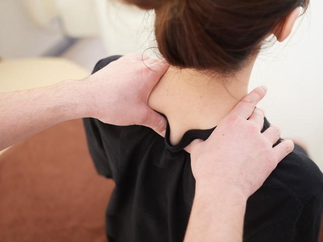 首のツボを押してもらっている女性の写真